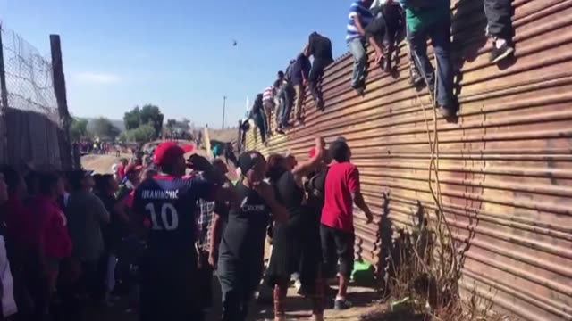 cientos de centroamericanos de la caravana migrante intentaron el domingo saltar la valla fronteriza que separa a mexico y estados unidos en medio de... - refugee stock videos & royalty-free footage