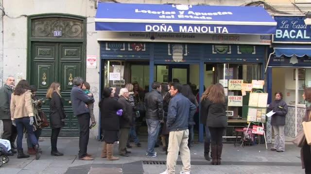 vídeos y material grabado en eventos de stock de cientos de espanoles hacen cola para comprar su decimo de loteria esperan que el tradicional sorteo de el gordo de navidad les traiga suerte en un... - artículos de lotería