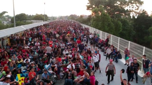 stockvideo's en b-roll-footage met cientos de migrantes centroamericanos que en caravana huyen de la pobreza y violencia la mayoria hondureños buscaban el lunes en un puente fronterizo... - puente