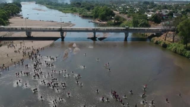 vídeos de stock e filmes b-roll de cientos de migrantes centroamericanos que quieren llegar a estados unidos intentaban cruzar el lunes a méxico desde guatemala mientras eran... - américa latina