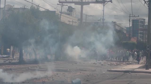 vídeos de stock e filmes b-roll de cientos de policias emplearon el domingo en honduras bombas lacrimogenas para disperar a mas de 1000 personas que marchaban paralelamente al desfile... - para choques