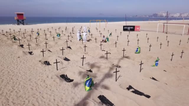 cientos de tumbas fueron cavadas simbólicamente en la playa de copacabana, en río de janeiro, para rendir homenaje a los miles de brasileños que... - digging stock videos & royalty-free footage