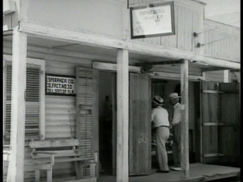 cigar shop w/ men standing in doorway int two men sitting at cigar bench rolling cigars handmade - 1934 stock-videos und b-roll-filmmaterial