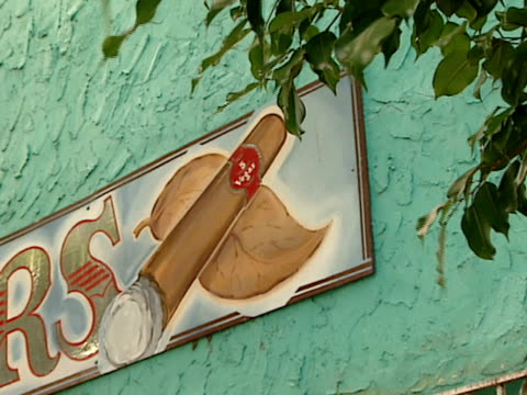 cigar sign hangs on the outside of a green stucco building. - intricacy stock videos & royalty-free footage