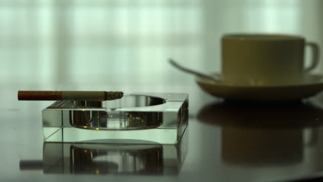 cigarette and coffee cup on table