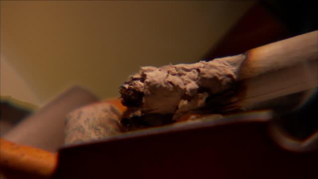 a cigarette burns in an ashtray near a glass of ice. - aschenbecher stock-videos und b-roll-filmmaterial