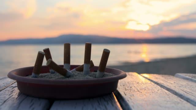 zigarettenbluttat in ashtray auf see. schöner sonnenuntergang bei griechenland - zigarettenstummel stock-videos und b-roll-filmmaterial