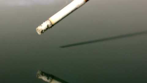 cigarette falling onto reflective surface - cigarette stock videos & royalty-free footage