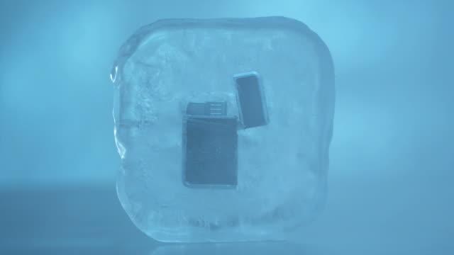 cu cigarette lighter frozen in ice cube. - feuerzeug stock-videos und b-roll-filmmaterial