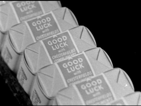 cigarettes moving by on conveyor w/ 'good luck' seal. dramatization: us servicemen sitting w/ sandbags bg, two smoking cigarettes, other soldier fg... - luck stock videos & royalty-free footage
