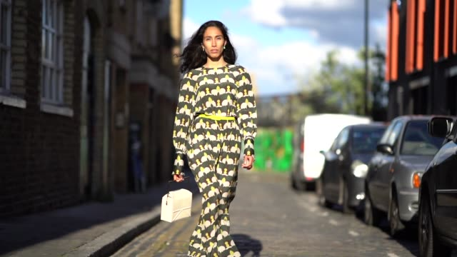 ciinderella balthazar wears a green and yellow dress with printed geometric patterns, a white bag, yellow heels shoes, during london fashion week... - ストリートスナップ点の映像素材/bロール