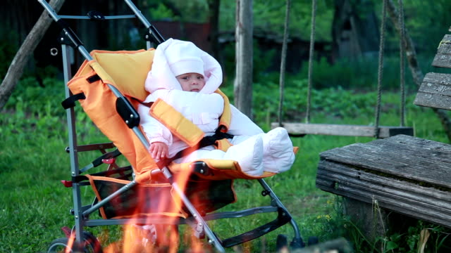 cild sitting in front of the campfire in the pram - looking through an object stock videos & royalty-free footage