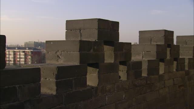 vidéos et rushes de cinder blocks form a wall above a neighborhood in beijing. - parpaing