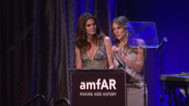 Cindy Crawford and Elizabeth Hurley present an auction item at amfAR New York Gala To Kick Off Fall 2012 Fashion Week on in New York
