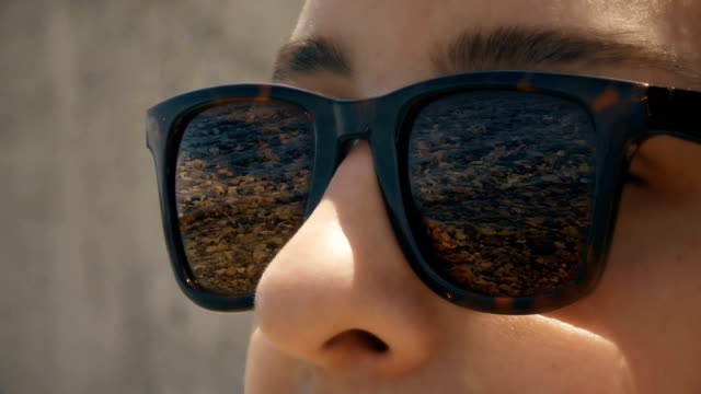 cinemagraph - a woman in sunglasses with a reflection of seashore - sunglasses stock videos & royalty-free footage