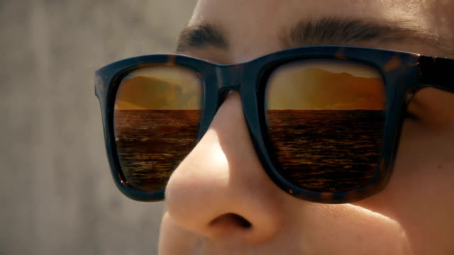 cinemagraph - a woman in sunglasses with a reflection of sunset waves - sunglasses stock videos & royalty-free footage