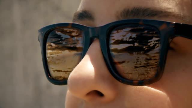 vidéos et rushes de cinémagraphe - une femme dans des lunettes de soleil avec un reflet des vagues dans le coucher du soleil - lunette soleil