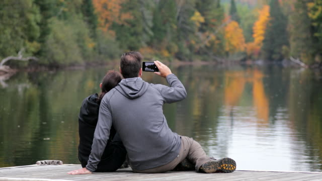 cinemagraph, adult couple having fun on wooden dock in autumn and taking pictures with mobile phone - autumn stock videos & royalty-free footage