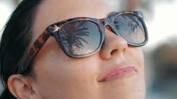 Cinemagraph - Beautiful young brunette smiling girl in retro sunglasses in the tropical vacation. Palm trees reflection in glasses. Travel concept. Slow motion