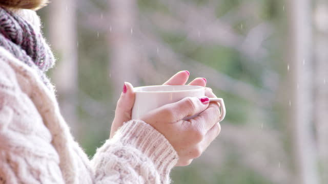 4k cinemagraph close up of woman drinking hot chocolate and watching snow falling, slow motion - winter video stock e b–roll