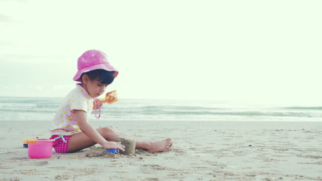 cinemagraph : cute girl play sand and happy on the beach - wide shot stock videos & royalty-free footage