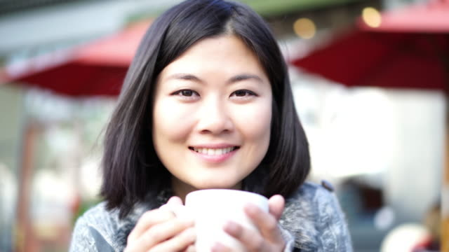Cinemagraph, Drinking coffee at pavement cafe. Asian woman smiling.