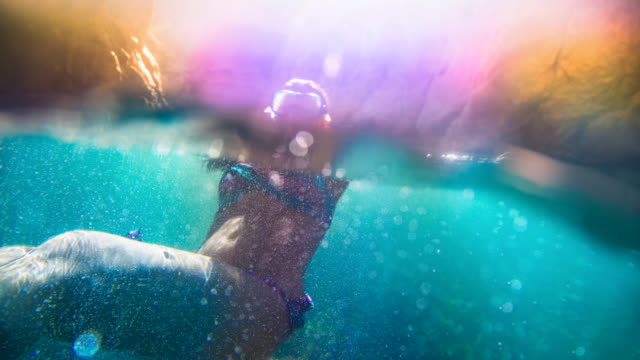 cinemagraph effect of a beautiful girl doing snorkel with colorful bikini in the mediterranean waters of costa brava on summer with underwater bubble motion view in an idyllic place with vivid colors. - 25 29 jahre stock-videos und b-roll-filmmaterial