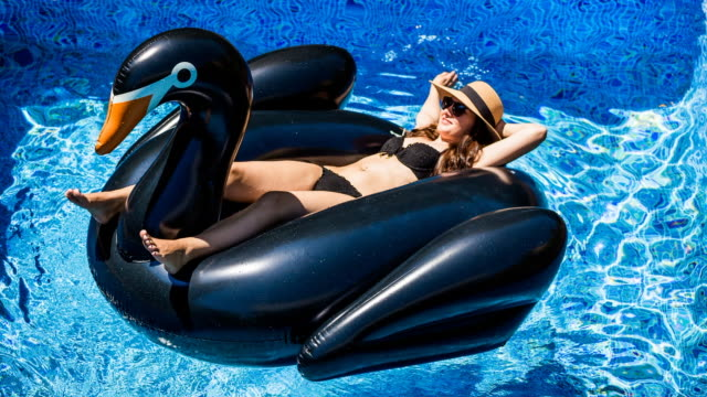 Cinemagraph effect of a happy girl enjoying summer in swimming pool with big inflatable black swan sunbathing and relaxing in the sun during weekend.