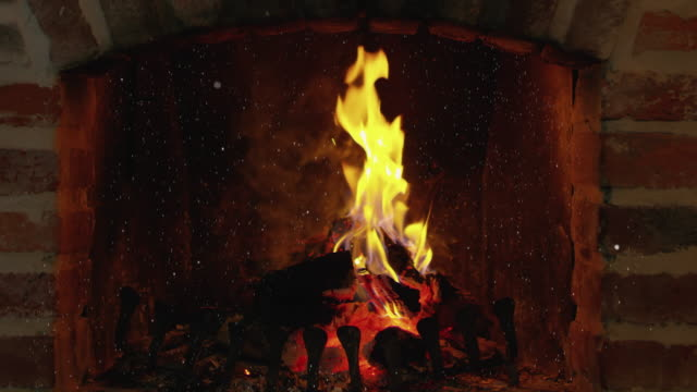 ws cinemagraph effect of a snow falling over a fireplace - fuoco acceso video stock e b–roll