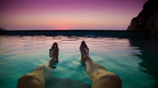 cinemagraph effect of  a stunning footage of guy floating on water from personal perspective with legs and feet contemplating the sunrise from swimming pool in the mediterranean sea costa brava during travel vacations. - infinity pool stock videos & royalty-free footage