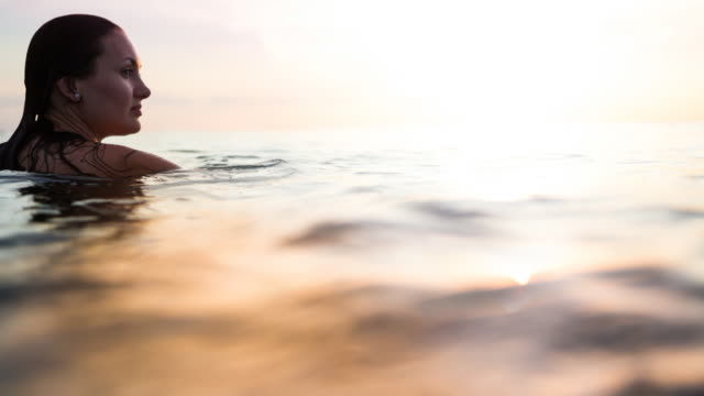 Cinemagraph effect of a traveler woman floating on water resting during sunset moment after long day during travel vacations in the paradise islands of Indonesia with stunning colors in the sky and reflections on water.