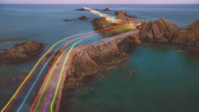 Cinemagraph effect of long exposure with colorful rainbow of light traces in a beautiful curved path between the rocks over the Mediterranean Sea in the Costa Brava shoreline on sunset.