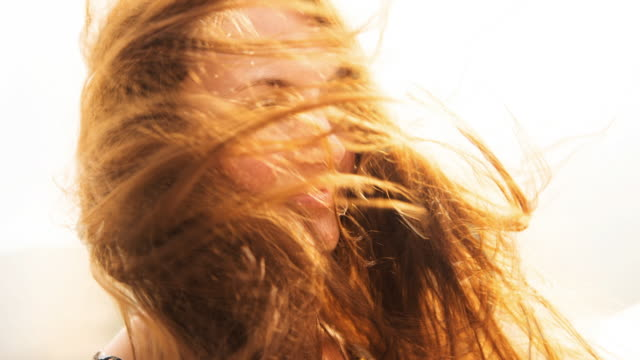 Cinemagraph effect of the hair of beautiful woman in motion during windy day in the Costa Brava during travel vacations in Catalonia.