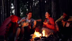 Cinemagraph loop - young man tourist is playing the guitar while his friends are singing and laughing sitting around fire in the wood in the evening enjoying nature and company.