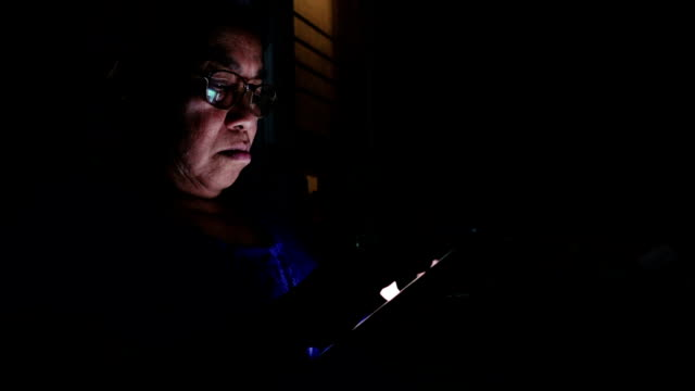 Cinemagraph : Mature woman using her tablet at home in the dark.