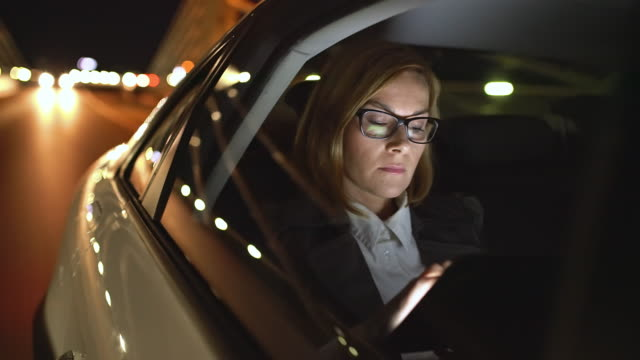 ws cinemagraph of a businesswoman using a tablet on the back seat of a car - driver occupation stock videos & royalty-free footage