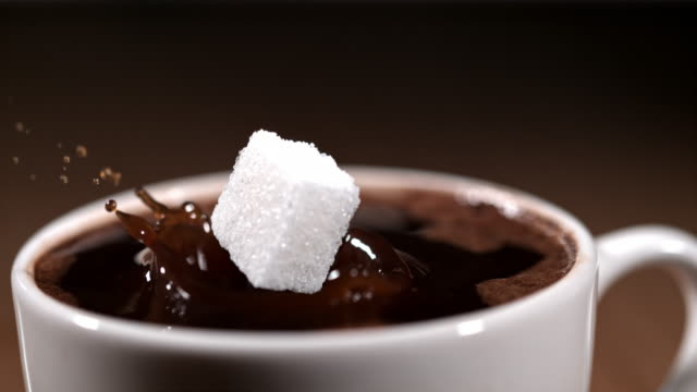 slo mo cinemagraph of a cube of sugar floating above a coffee - sugar stock videos & royalty-free footage