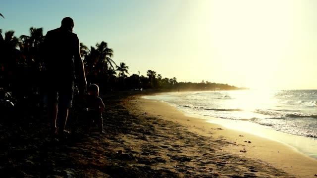 浜辺の砂の上に立っている父とその幼い赤ん坊のシネマグラフ。 - シネマグラフ点の映像素材/bロール