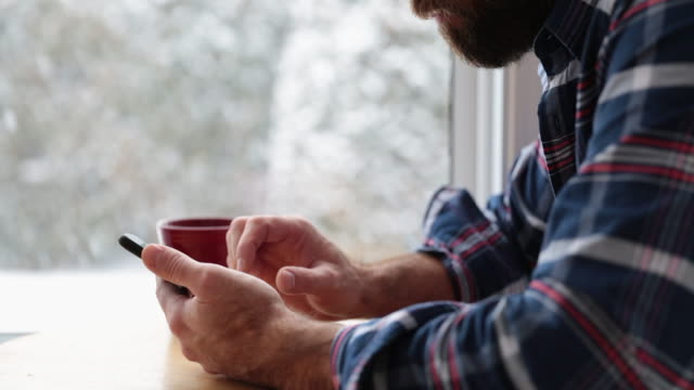 cinemagraph of a man sitting in coffee shop using smart phone - text messaging stock videos & royalty-free footage