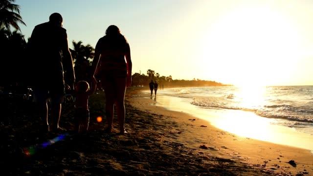 cinemagraph av en mor och far med deras unga barn som står i sanden vid stranden. - cinemagrafi bildbanksvideor och videomaterial från bakom kulisserna