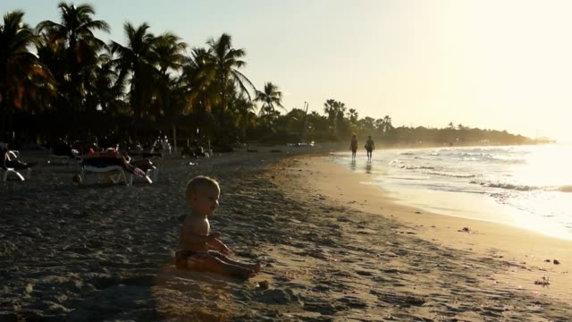 cinemagraph of a young baby sitting in the sand by the beach. - varadero beach stock videos and b-roll footage
