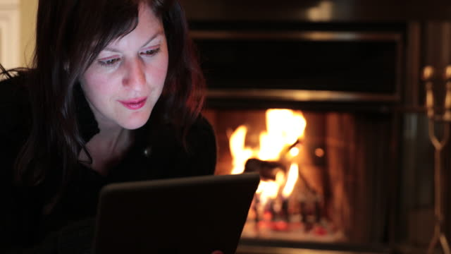 cinemagraph of a young woman using digital tablet by fireplace - cosy stock videos & royalty-free footage