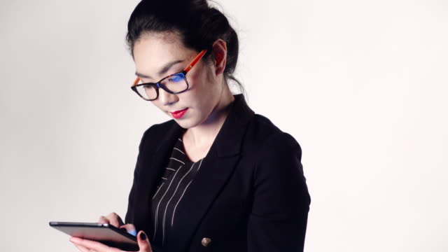 Cinemagraph of asian businesswoman using tablet on white background.