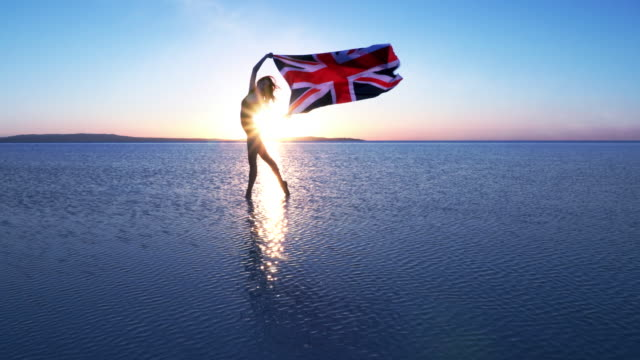 cinemagraph of beautiful dancer holding a british flag on the lake. a windy day. - bandiera del regno unito video stock e b–roll