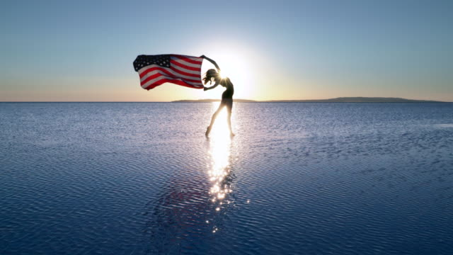 Cinemagraph of beautiful dancer holding a US flag on the lake. A windy day.