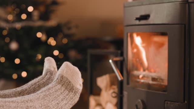 cinemagraph fötter upp framför den öppna spisen vid jul - cinemagrafi bildbanksvideor och videomaterial från bakom kulisserna