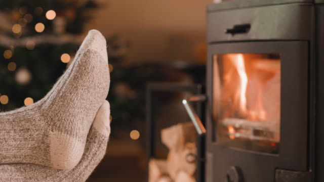 cinemagraph of feet up in front of the fireplace at christmas - cozy stock videos & royalty-free footage