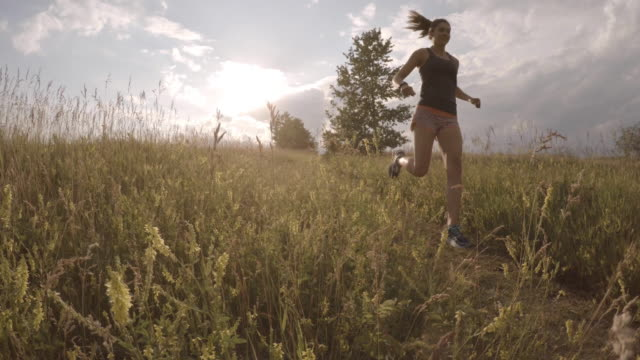 Cinemagraph of female trail runner traversing meadow