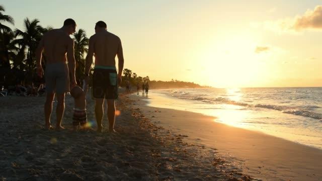 cinemagraph av homosexuella gudfäder med sin unge brorson som står i sanden vid stranden. - cinemagrafi bildbanksvideor och videomaterial från bakom kulisserna