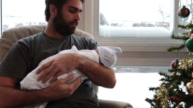 Cinemagraph of Loving Dad With Newborn Baby Close to Window in Winter
